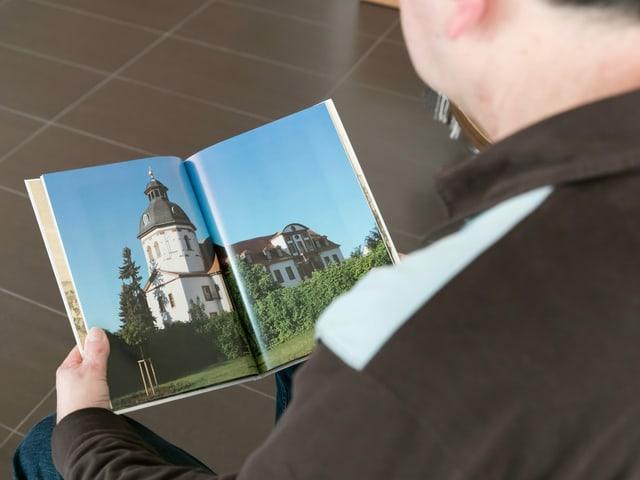Ein Mann betrachtet ein Buch mit Bildern aus Thüringen.