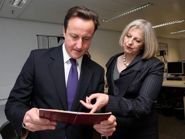 Theresa May zeigt David Cameron echte und gefälschte Pässe.