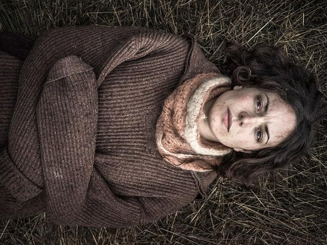 Eine Frau liegt auf dem Waldboden.