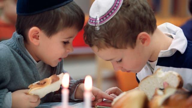 Zwei jüdische Kinder schauen gemeinsam etwas an.