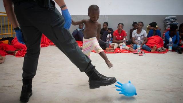 ein Polizist der Guarda Civil spielt mit Kind.