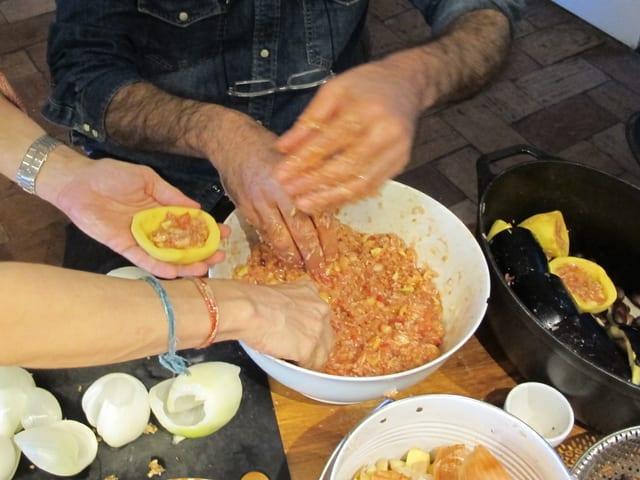 Zwei Paar Hände füllen Gemüse mit Reis in Tomatensauce
