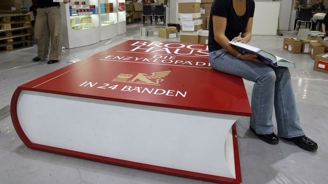 Eine Frau sitzt auf der überdimensionalen Attrappe eines Lexikons und liesst in einem Buch.