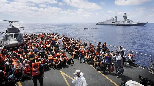 Flüchtlinge sitzen auf einer Plattform.