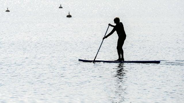 Ein Mann steht auf einem Brett, einem Stand-Up-Paddle auf dem Pfäffikersee. In der Hand hält er ein Paddel.