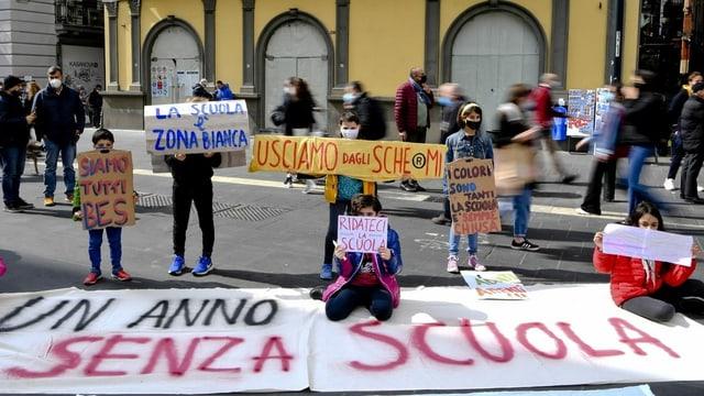 Schülerinnen und Schüler halten Protestplakate hoch.