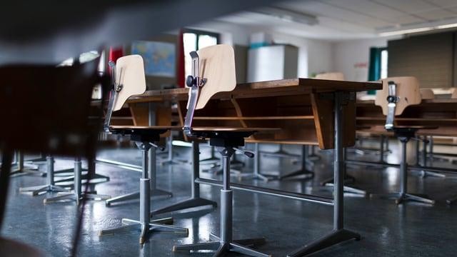 Schulbänke und Stühle in einem leeren Schulzimmer.