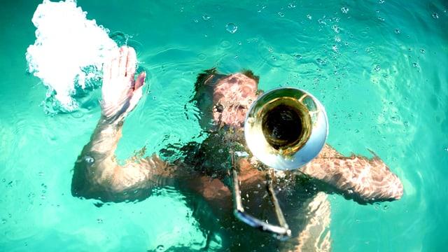 Ein Mann ist unter Wasser und streckt eine Posaune in die Luft.