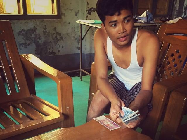 Ein junger Mann mit einem Geldbündel in der Hand sitzt an einem Tisch.