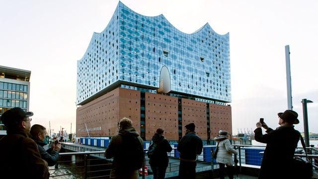 Blick von aussen auf die Elbphilharmonie. Pasanten fotografieren das Gebäude.