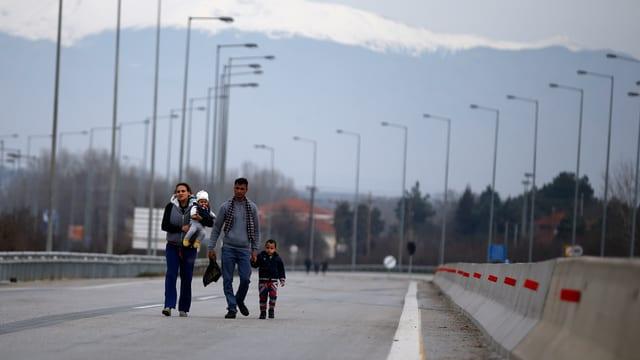 Vierköpfige Flüchtlingsfamilie zu Fuss auf einer Strasse an der griechisch-bulgarischen Grenze.