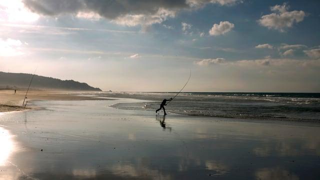 Ein Mann fischt am Strand.