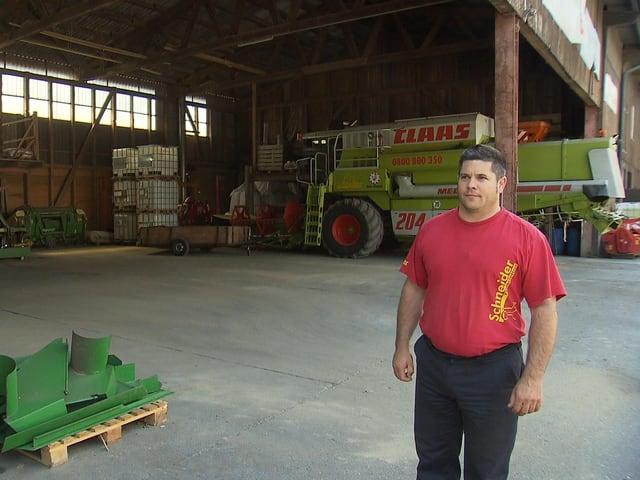 Bauer steht vor einer Maschine.