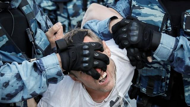 Protestierende wird von Polizisten festgehalten