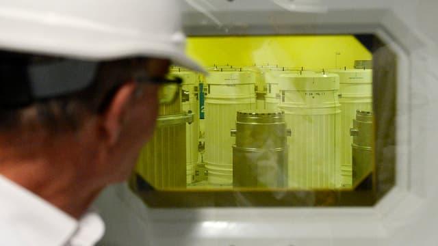 Ein Mann schaut durch ein Fenster in einen Raum mit Fässern und gelbem Licht