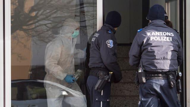 Drei Polizisten am Tatort in Hausen.