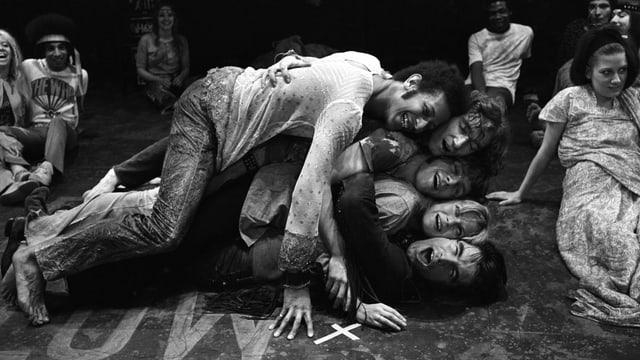 Fünf Leute liegen aufeinander.