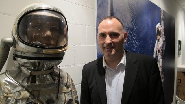 Ein Mann präsentiert einen Astronautenanzug.