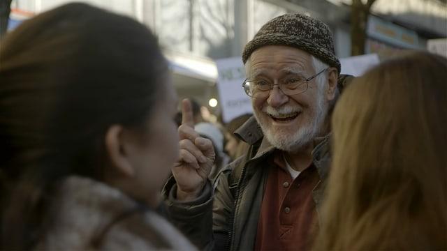 Jacques Dubochet unterhält sich während einer Demonstration mit jungen Klima-Aktivistinnen.