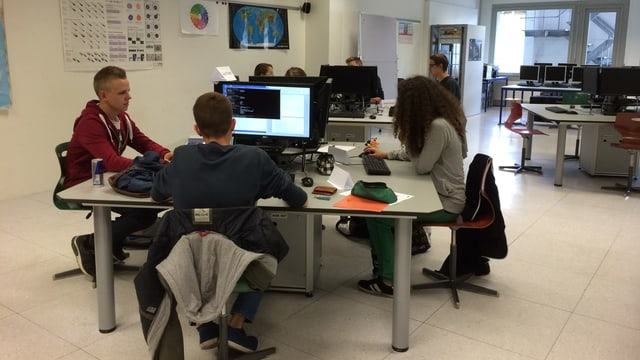 Lehrlinge sitzen am Pult und arbeiten am Computer