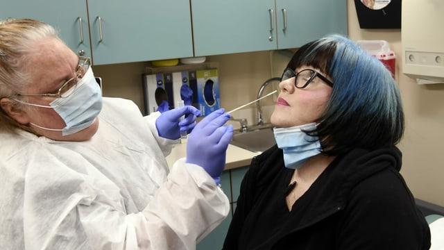 Eine Ärztin testet eine Patientin auf Corona.