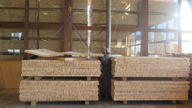 Zwei Stapel Holz, Kran transportiert Holz.