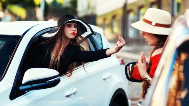 Frau lehnt aus dem Autofenster und zeigt einer anderen Frau den Stinkefinger.