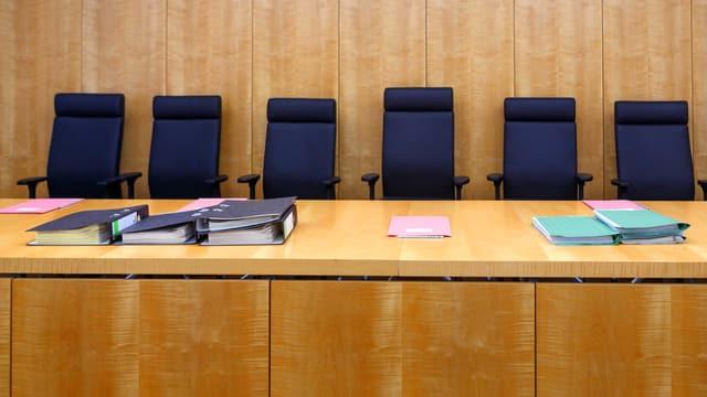 Leere Richterstühle eines Gerichtsraumes.