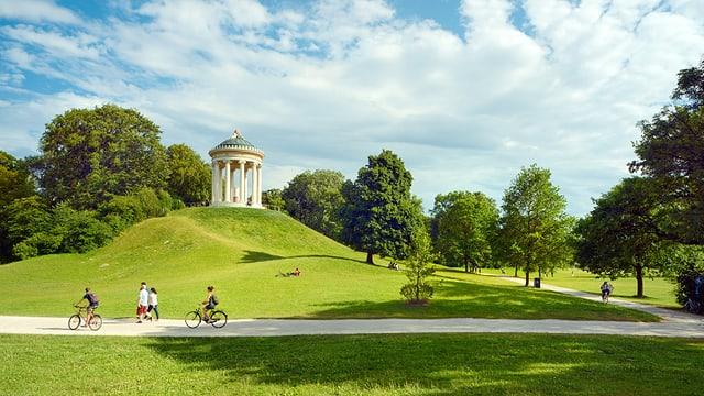 Ein grüner Park mit Fahrradfahrerinnen.