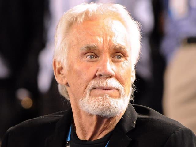 Ein Mann mit weissen Haaren, Bart und blauen Augen.