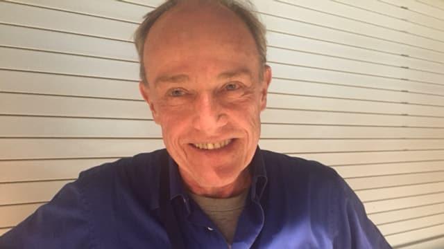 Portrait eines lächelnden Mannes mit Halbglatze.