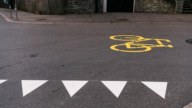 Eine Strasse mit Vortrittsrechtsenzug, dahinter eine gelbe Velomarkierung.