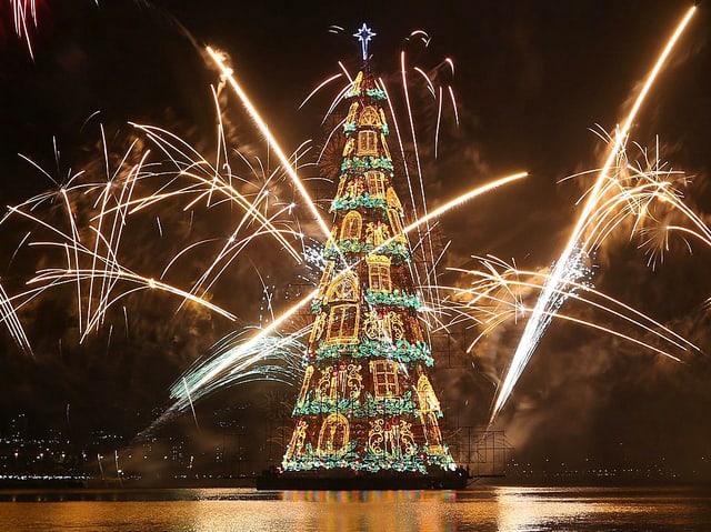 Ein hell erleuchteter Weihnachtsbaum. Feuerwerk wird abgefeuert.