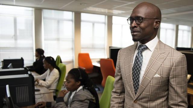 Ein Afrikaner in einem Anzug mit Krawatte in einem Büro.