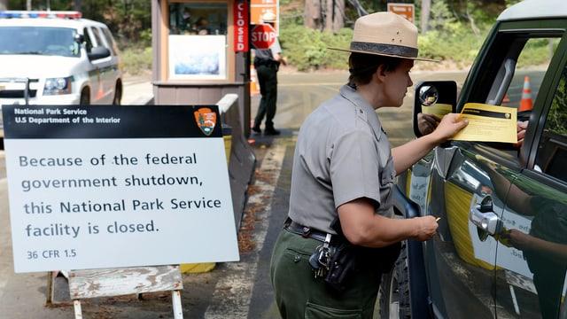Eine Nationalpark-Angestellte überprüft einen Autofahrer.