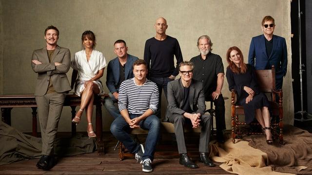 Ein Gruppenfoto: Neun Menschen sitzen und stehen beieinander, ganz rechts steht ein Mann in Anzug un dmit dunkler Sonnenbrille.