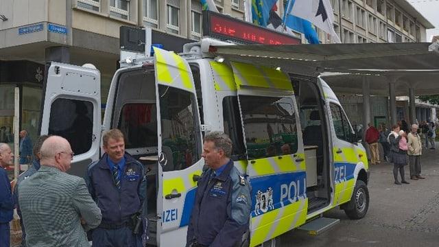 Zwei Polizisten im Gespräch am Claraplatz vor dem mobilen Polizeiposten