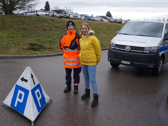 Verkehrskadett Noah und Moderatorin Anna bei einem Einsatz auf dem Parkplatz des Zürich Zoo.