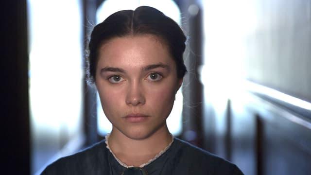 Eine junge Frau im Porträt. Sie blickt sehr ernst in die Kamera.