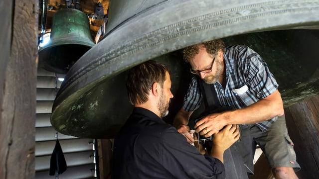Peter Conradin Zumthor und Gabriel Schneider umwickeln den Klöppel einer Glocke mit Teilen eines Motorradpneus.
