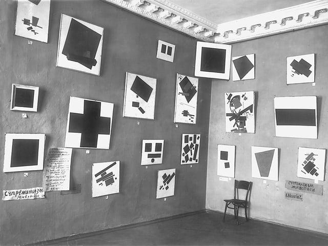 Schwarz-Weiss-Aufnahme: Zahlreiche abstrakte Gemälde in einem Ausstellungsraum.