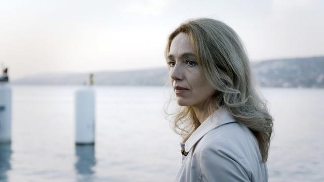 Eine blonde Frau steht am Ufer eines Sees.