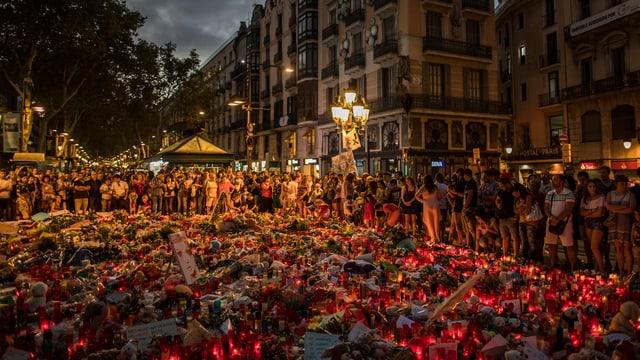 Meer von Blumen und Kerzen am Ort des Anschlags mit vielen Menschen im Hintergrund