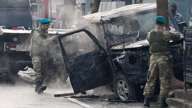 Zwei Soldaten vor einem ausgebrannten Auto.