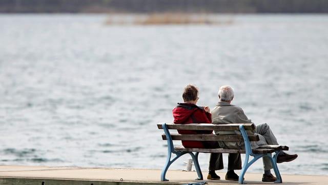 Zwei alte Menschen mit dem Rücken zur Kamera sitzen auf einer Bank und schauen aufs Wasser hinaus.
