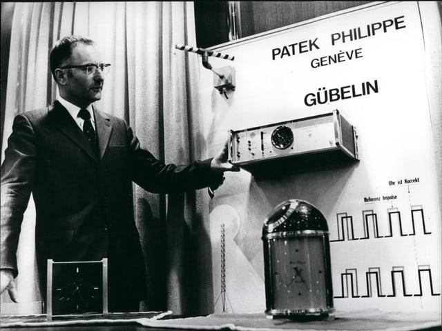 Ein Mann präsentiert eine weckergrosse Quarz-Uhr, die mit einer Atomuhr im Hintergrund via Radiowellen verbunden ist.