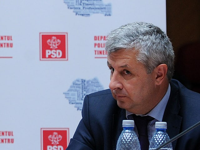 Florin Iordache an einer Pressekonferenz. Er hat einen irritierten Gesichtsausdruck.