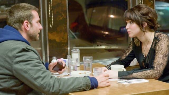 Bradley Cooper und Jennifer Lawrence sitzen sich in einem Diner gegenüber.