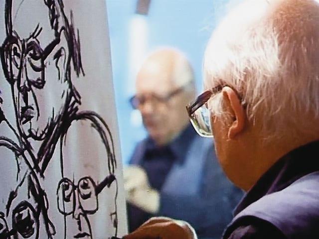 Friedrich Dürrenmatt wird gespiegelt fotografiert, wie er ein Selbstporträt zeichnet.