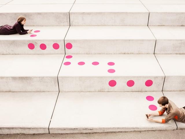 Ein Mann und eine Frau liegen auf unterschiedlichen Studen einer grossen Treppe. Sie haben beide ein Smartphone in der Hand. Verbunden werden sie durch eine gepunktete Linie über die Treppe.